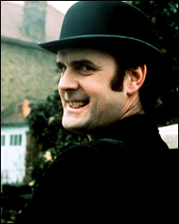 John Cleese, wearing a bowler hat and pulling a funny face.