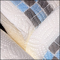 A close-up of the perforated surface of some kitchen rolls.