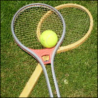 A pair of tennis racquets and a ball.