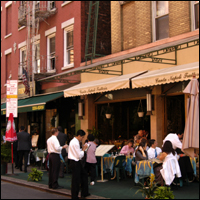Diners sitting at tables on the pavement in Little Italy, New York.