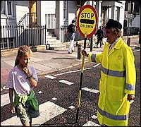 A 'lollipop lady' showing some children across the road.