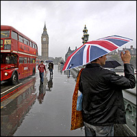On a typically rainy London day, a red double-decker bus crosses Westminster Bridge and a tourist, carrying a Union Flag umbrella, takes a photo.