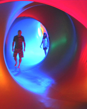 Two people walking through the magically-lit cave-like structure of a luminarium
