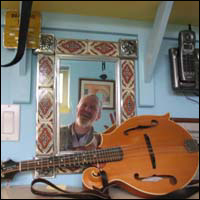 A mandolin in the foreground; the reflection in a mirror of the mandolin's owner in the background.