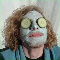 A man wearing a skin-purifying face mask, with cucumber slices over his eyes.