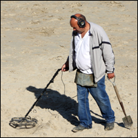 A man combing the beach with his metal detector.