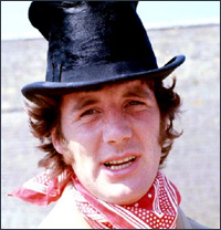 Michael Palin squinting into the summer sun, a top hat on his head, a red necktie blowing in a rather gentle breeze.