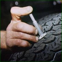A mechanic testing a tyre's tread depth.