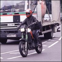 Someone on a motorbike in London traffic.