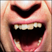 Close-up of a man's open mouth expressing anger.