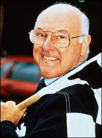 Murray Walker holding a black and white-checkered finishing flag.