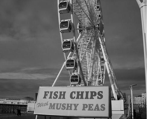 A sign for fish and chips with mushy peas in front of a Ferris Wheel.