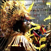 A dancer in a golden head dress as part of the Notting Hill Carnival parade.