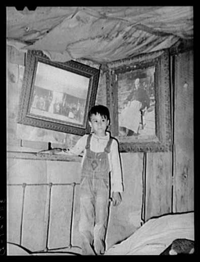 An American Indian boy with ancestral portraits.