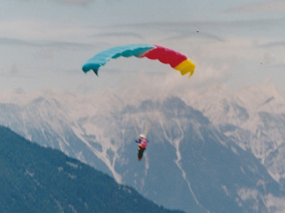 Photo of paraglider flying above mountains.