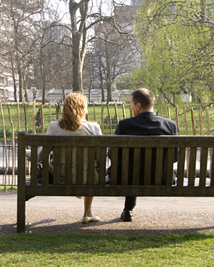 A man and a woman sat on a bench in St James' Park, London