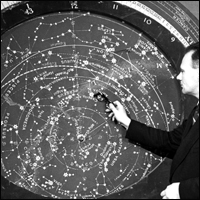 Astronomer Patrick Moore pointing to stars in our galaxy on a planisphere.