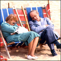 Two pensioners asleep on deckchairs on Bournemouth beach.