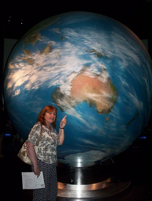A woman pointing to a very big globe.