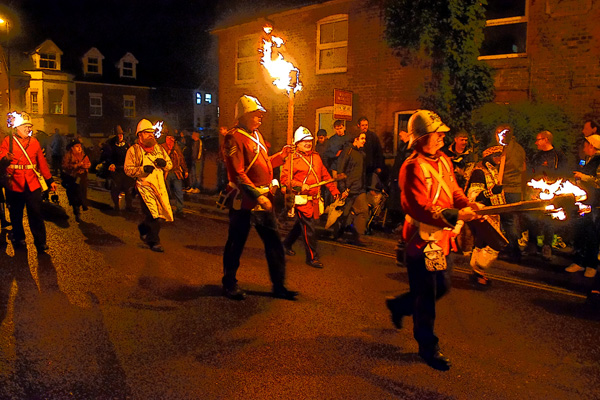 A picture of redcoats carrying torches marching through town