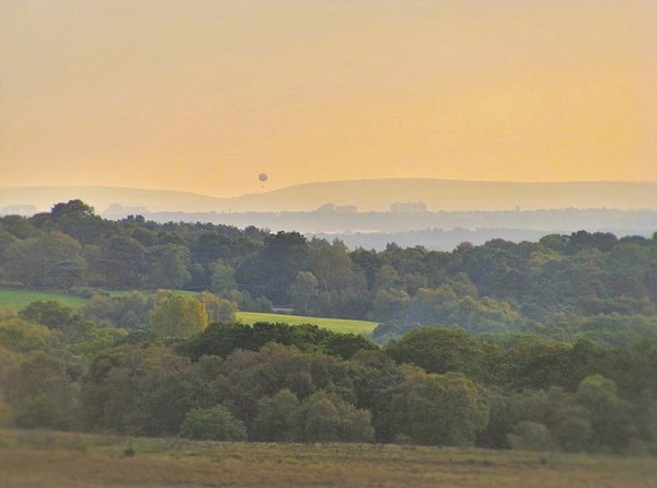 A wide vista showing rolling hills and valleys, an orange-tinted sky, and a gas balloon floating above the hills