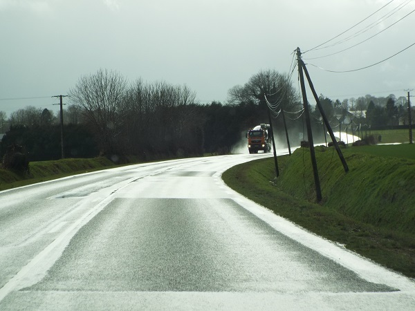 A lorry at a bend in a rainy road.