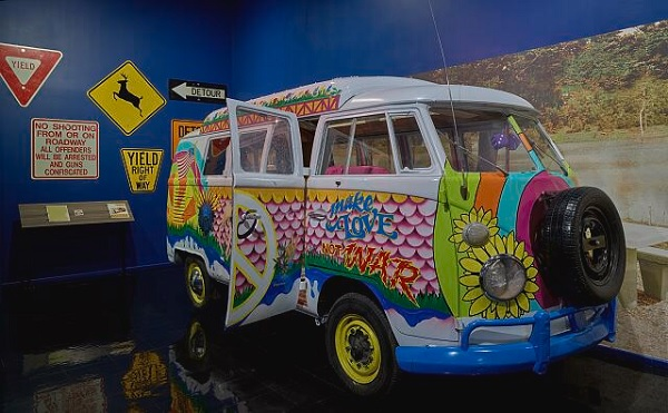 A VW hippie bus, brightly decorated, in a museum. By Carol M Highsmith.