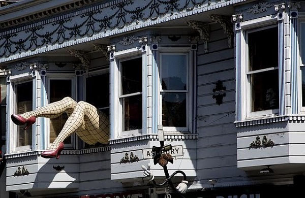 Strange art installation consisting of a giant pair of woman's legs in high heels and fishnet stockings, sticking out of an upstairs window in a house in the Haight Ashbury district of San Francisco