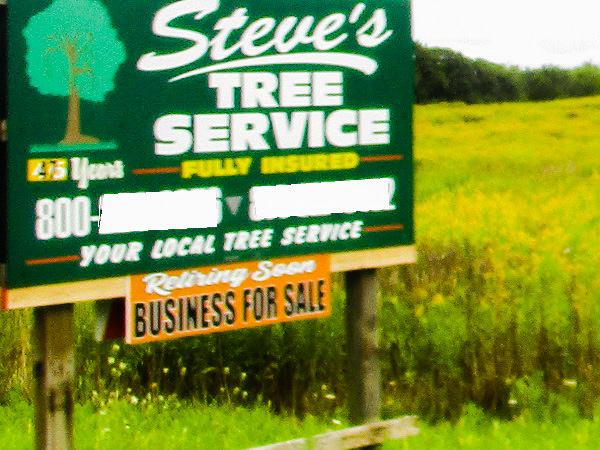 A sign for a tree service beside a field, by DG.
