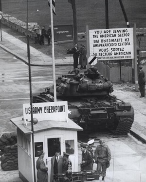Checkpoint Charlie, the Cold War crossing point between East and West Berlin, with soldiers showing their papers and a tank parked nearby.