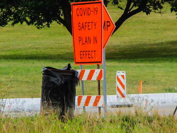 Highway Sign Saying 'Covid Safety Plan in Effect' Next to a Trash Barrel by Dmitri Gheorgheni