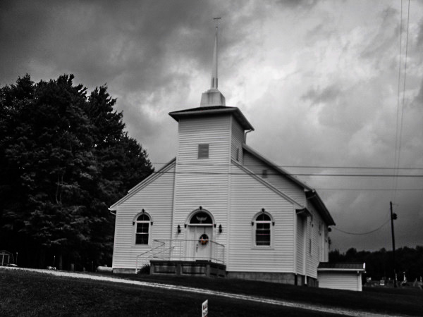 A white wooden church with steeple on an isolated country road in Pennsylvania, with storm clouds in the background.