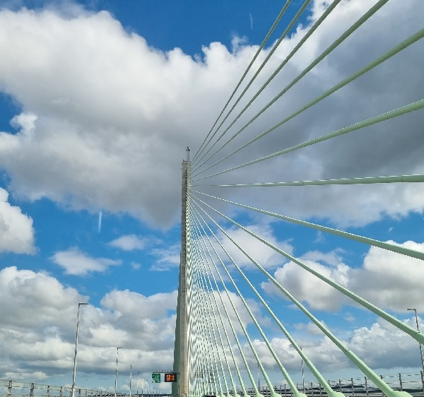 Suspension bridge cables in the sun lead the eye to clouds that may conceal a UFO, by FWR, who's always seeing UFOs.