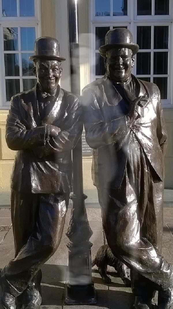 A statue of Laurel and Hardy, with a ghostly third figure, by Galaxy Babe.