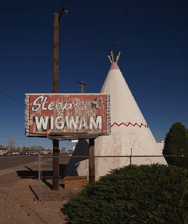 Sign that says Sleep in a Wigwam next to a unit of the Wigwam Motel, which is a motel room in a building shaped like a wigwam.