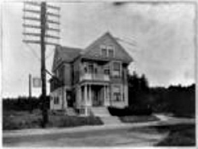 A house in the country in 1910, showing what it was like to be next to a telegraph pole with six crossbars and lots of wires.
