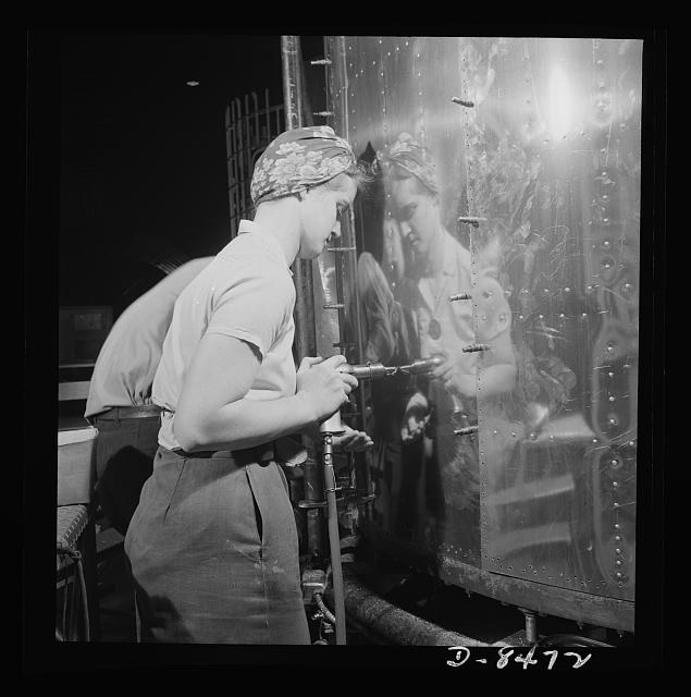 A very clever photo of a woman riveter at the Boeing plant in the 1940s. The riveter is reflected in the metal surface she's working on. Women replaced men in a lot of factory jobs during the Second World War. Photographers and reporters found this so amazing that they were constantly taking pictures and writing articles about it.