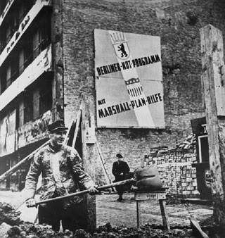 A man clearing away rubble in postwar Berlin, under a sign about the Marshall Plan.