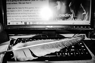 A quill pen lying atop a computer keyboard.