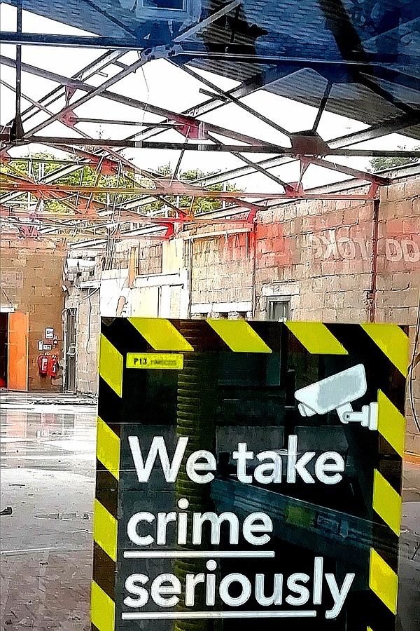 Store with a partially missing roof and the sign 'We Take Crime Seriously'