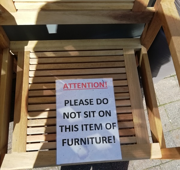 A furniture sign that says, Do not sit on the furniture. Paige wonders why anybody would bother to buy furniture they couldn't sit on. We think the same thing about those mattress tags that say 'Do Not Remove'.