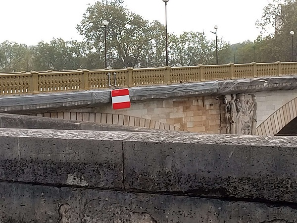 A canal or river flowing under a bridge. On the bridge is a sign that either means 'do not enter' or is the Austrian flag. Photo by Superfrenchie.