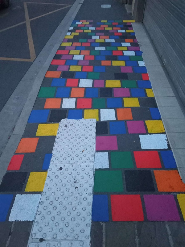 Colourful pavement made of a brick pattern painted in different colours. With a section of textured pavement.