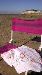 A deck chair and towel with beach view