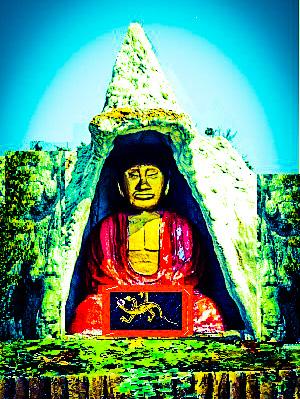 A buddha in a garden with a lizard brooch