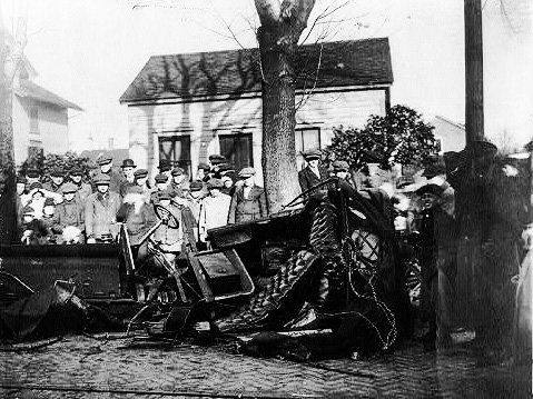 People staring at a wrecked car in 1913