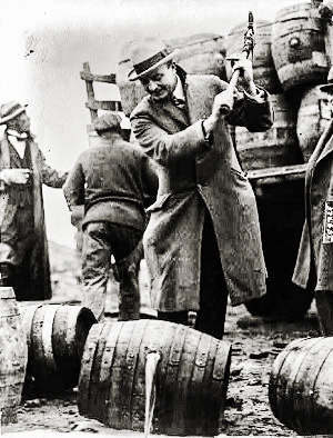 Man breaking up a barrel of beer with an axe on the banks of the Schuylkill River in Pennsylvania during Prohibition Era