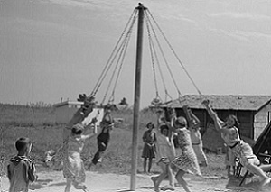 Children playing on a maypole.