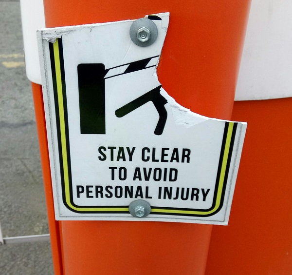 A damaged sign warning of the danger of personal injury.