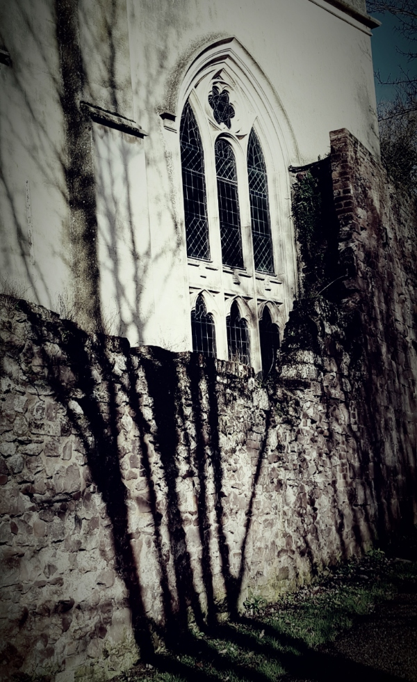 An old church by night, with a darkened stained glass window and shadows on the wall'
